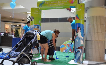 A mother putts with her son at our golf game challenge. He won a flying disc.